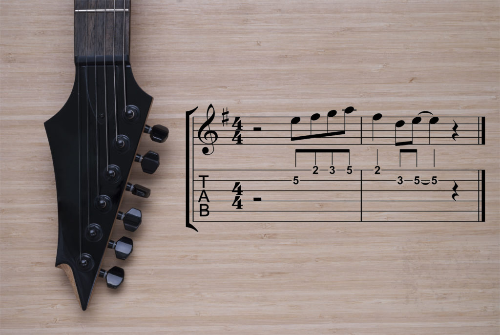 electric guitar fretboard on a wooden background texture